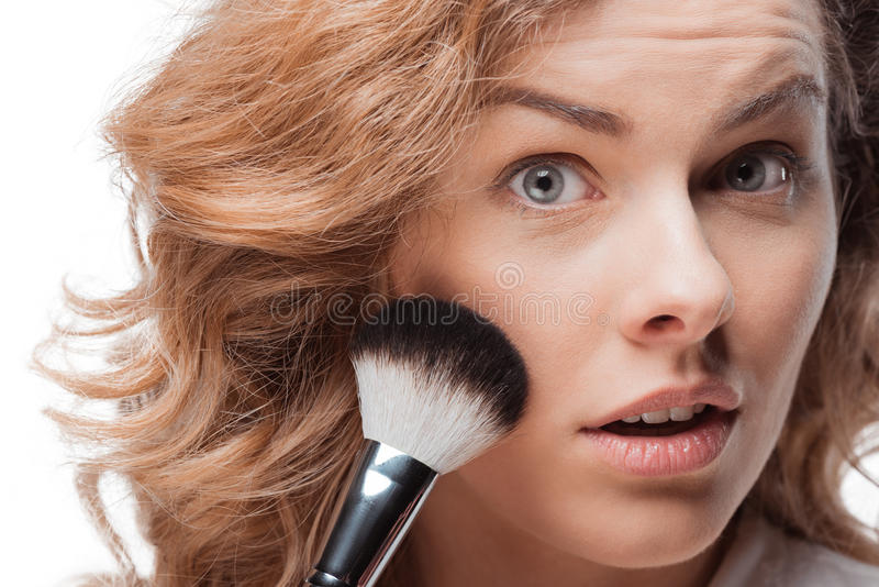 Mujer bastante rubia que aplica maquillaje con el cepillo foto de archivo