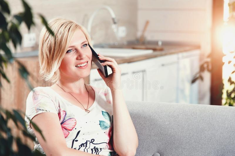 Mujer bastante rubia que habla en Smartphone foto de archivo libre de regalías
