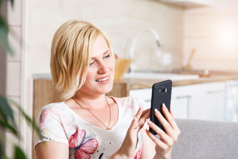 Mujer bastante rubia que usa el texto de Smartphone imagenes de archivo