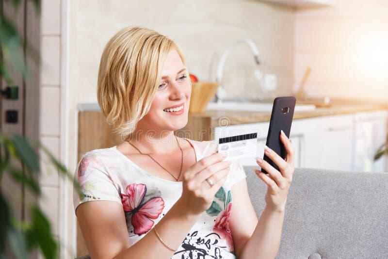 Mujer bastante rubia que usa la tarjeta de crédito con el teléfono fotos de archivo libres de regalías