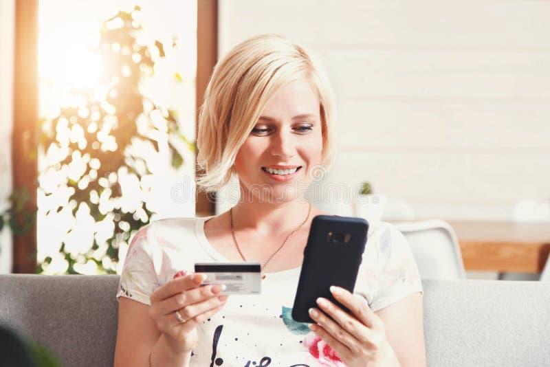 Mujer bastante rubia que usa la tarjeta de crédito con el teléfono imágenes de archivo libres de regalías