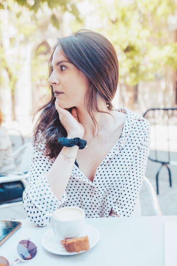 Mujer bastante seria y pensativa que espera mientras que bebe un café en la terraza en la ciudad fotos de archivo libres de regalías