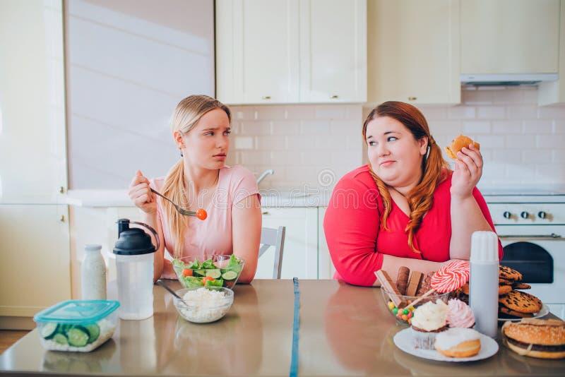 Mujer bien hecha joven distraída que come el queso y la mirada en el modelo del tamaño extra grande que sostiene la hamburguesa a imagenes de archivo