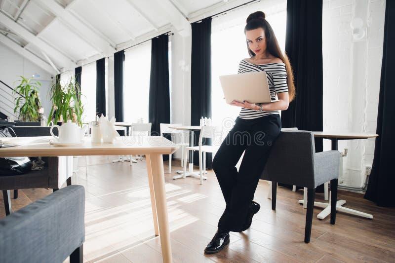 Mujer bien proporcionada preciosa en el traje de negocios que coloca la tabla cercana con el ordenador portátil Los soportes cerc fotografía de archivo