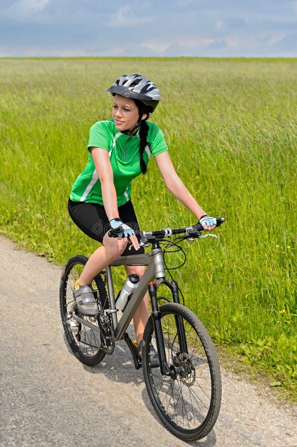 Mujer biking el día soleado del camino del campo fotos de archivo