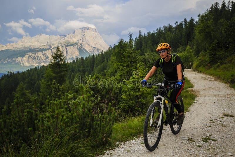 Mujer biking en dolomías, Italia de la montaña imagen de archivo