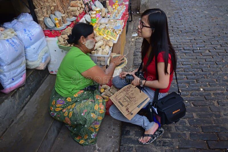 Mujer birmana que ayuda a aplicar la goma recién hecha de Thanaka a una muchacha turística extranjera joven foto de archivo libre de regalías