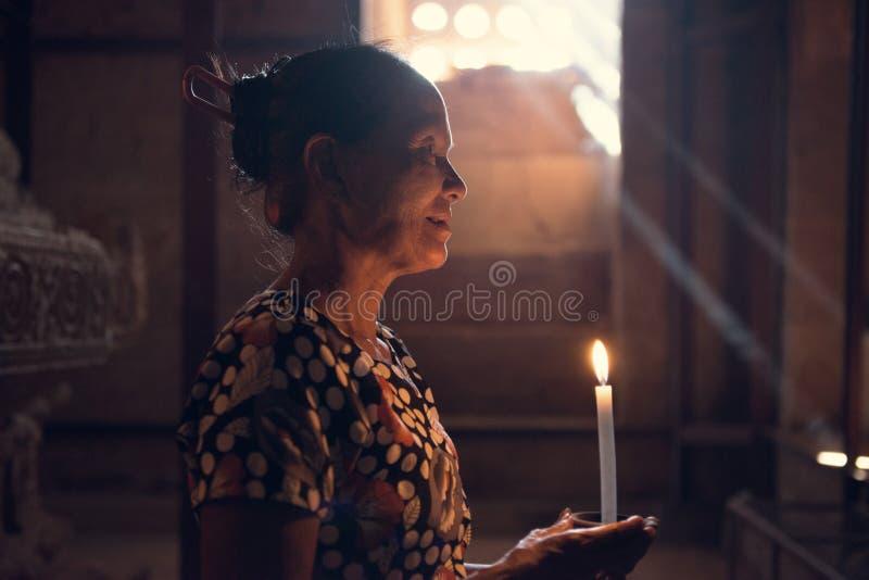 Mujer birmana que ruega con la luz de la vela imagenes de archivo