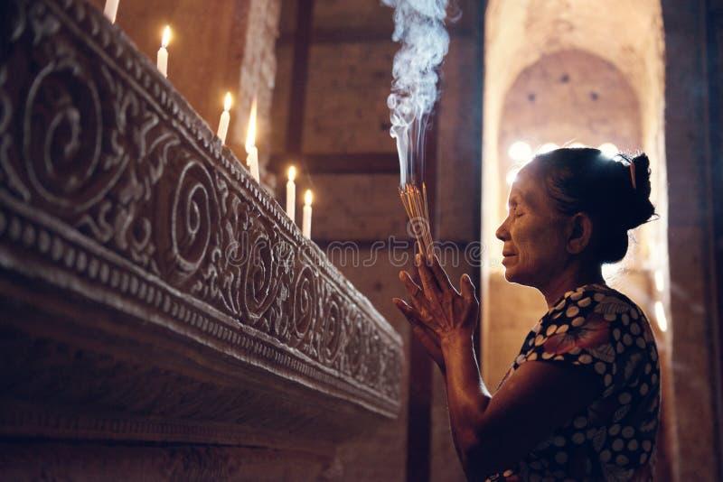 Mujer birmana que ruega en templo foto de archivo