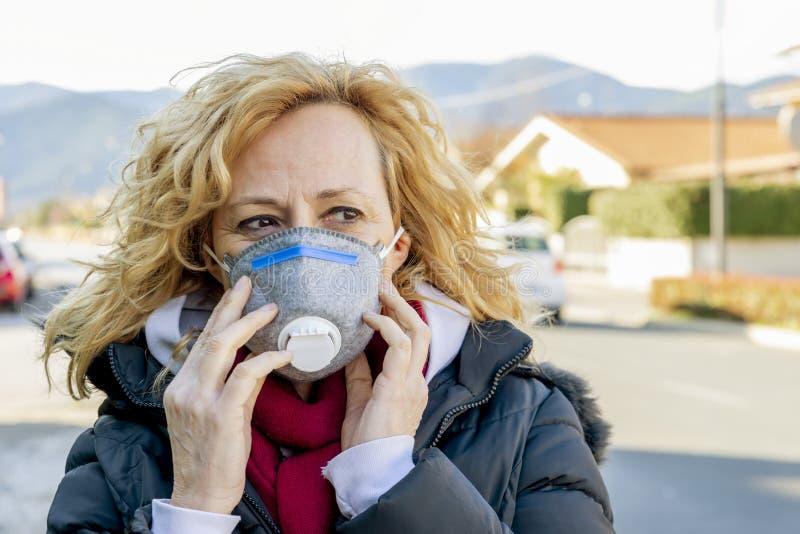 Mujer blanca camina por la calle con la máscara protectora en los tiempos del coronavirus 'Covid - 19' que está afectando a mucha imagen de archivo