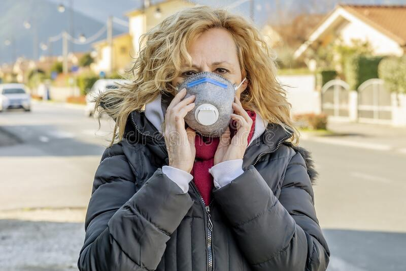 Mujer blanca camina por la calle con la máscara protectora en los tiempos del coronavirus 'Covid - 19' que está afectando a mucha fotografía de archivo libre de regalías