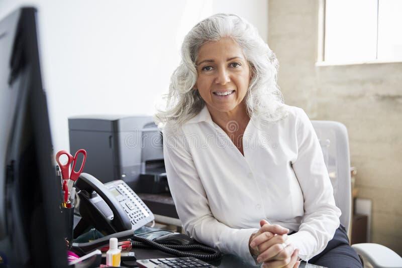 Mujer blanca mayor profesional en la oficina que mira a la cámara fotos de archivo