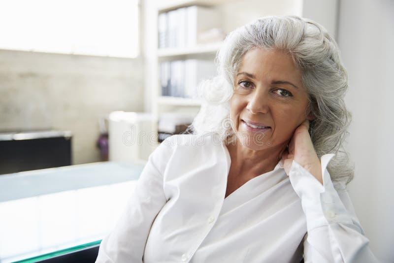 Mujer blanca mayor profesional en la oficina que mira a la cámara fotografía de archivo