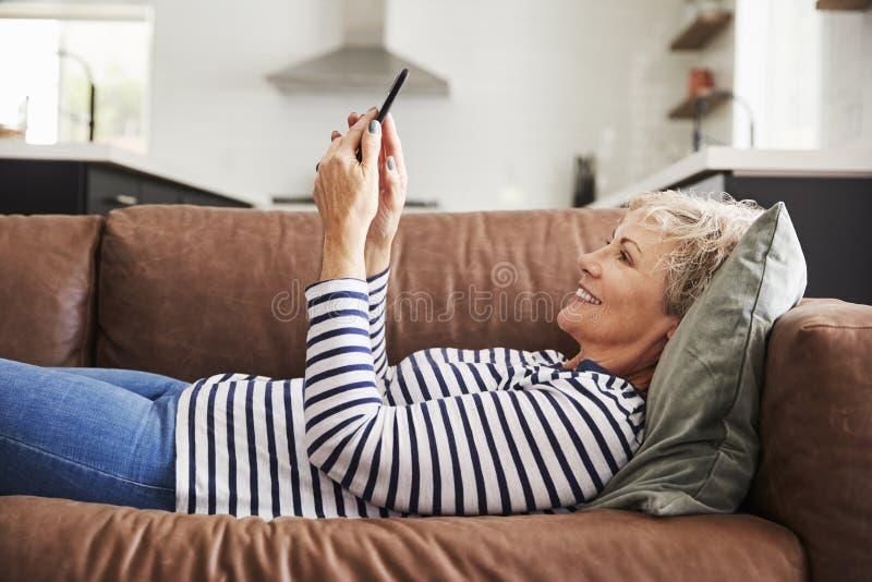 Mujer blanca mayor que miente en el sofá en casa usando smartphone fotos de archivo libres de regalías