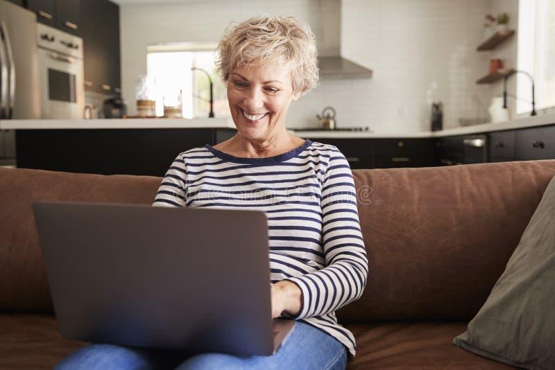 Mujer blanca mayor que se sienta en el sofá usando el ordenador portátil fotografía de archivo libre de regalías