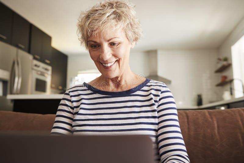 Mujer blanca mayor usando el ordenador portátil en casa, cierre para arriba fotos de archivo