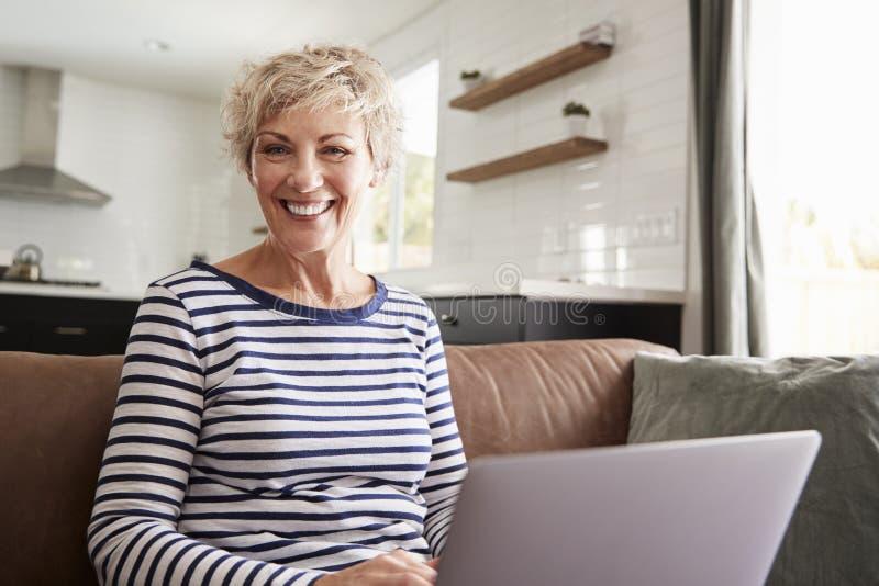 Mujer blanca mayor usando el ordenador portátil en casa, mirando a la cámara imagen de archivo libre de regalías