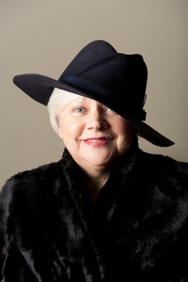mujer Blanco-cabelluda en sombrero negro y capa imagen de archivo libre de regalías