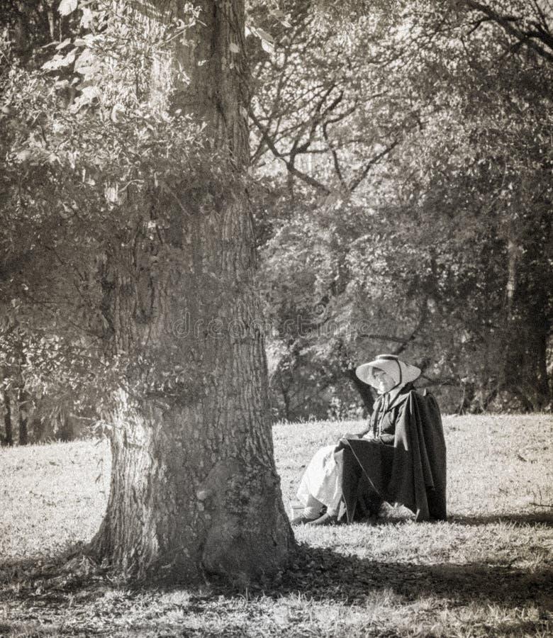 Mujer blanco y negro del estilo del vintage que toma el sol en el prado foto de archivo