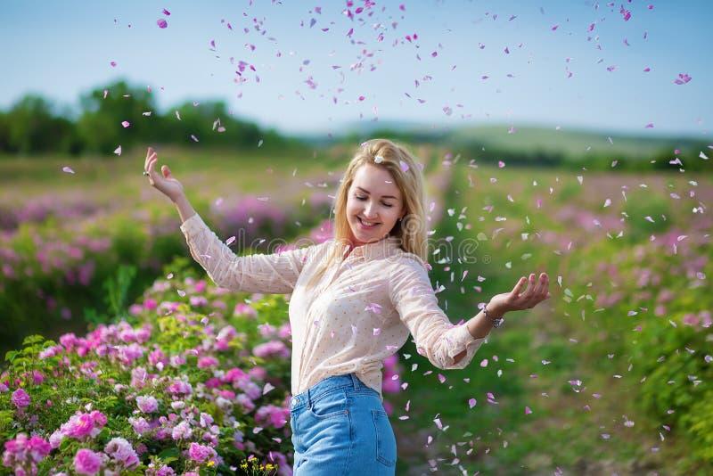 Mujer blanda joven bonita que camina en el campo de las rosas de té Los vaqueros que llevan de la señora rubia y el sombrero retr foto de archivo libre de regalías
