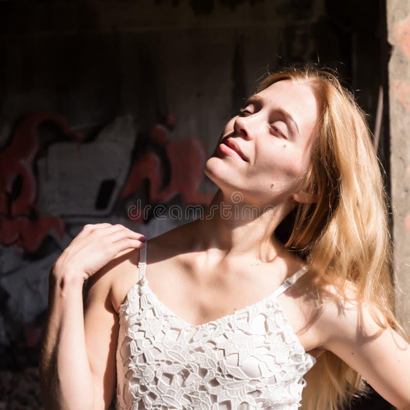 Mujer blondy sola en una blusa translúcida de la pizca en el edificio abandonado fotos de archivo libres de regalías