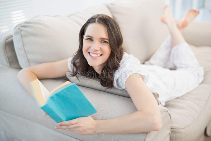 Mujer bonita alegre que miente en un libro de lectura acogedor del sofá fotografía de archivo libre de regalías