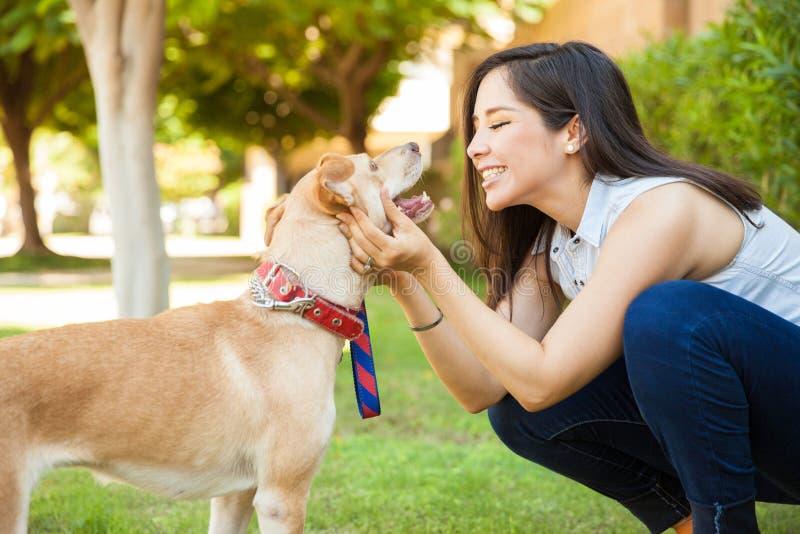 Mujer bonita alrededor para besar su perro foto de archivo libre de regalías