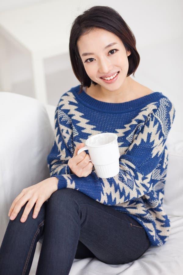Mujer bonita asiática joven que come una taza de café. foto de archivo libre de regalías