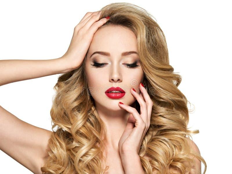 Mujer bonita con el pelo largo y los clavos rojos fotografía de archivo