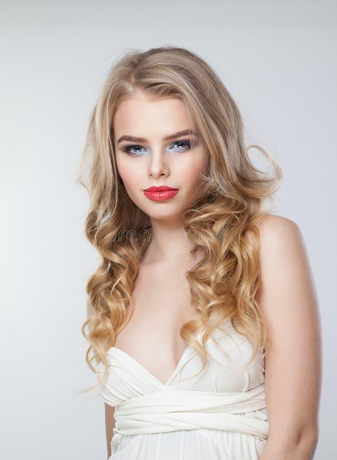 Mujer bonita con el pelo rizado rubio sano Modelo hermoso con maquillaje imagen de archivo