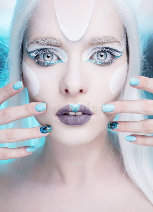 Mujer bonita con maquillaje de la reina de la nieve y el primer de los clavos fotos de archivo
