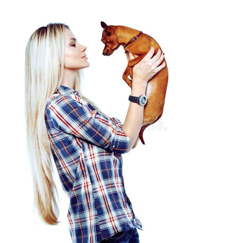 Mujer bonita con su pequeño perrito aislado sobre el backgroun blanco foto de archivo