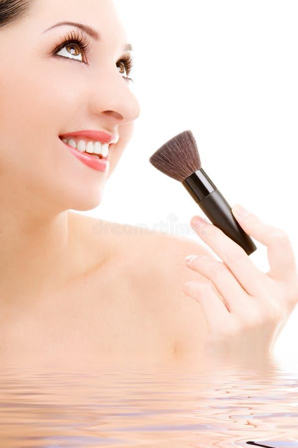 Mujer bonita con un cepillo del maquillaje imagenes de archivo