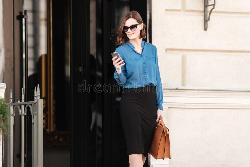 Mujer bonita confiada en gafas de sol usando el teléfono móvil imágenes de archivo libres de regalías