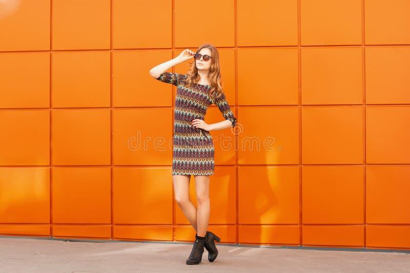Mujer bonita de la moda en vestido y gafas de sol Fondo de un bri foto de archivo
