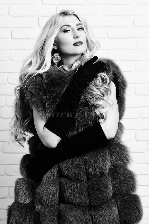 Mujer bonita de moda joven con el pelo rubio rizado largo hermoso en capa de la cintura de la piel azul y del terciopelo negro imagen de archivo