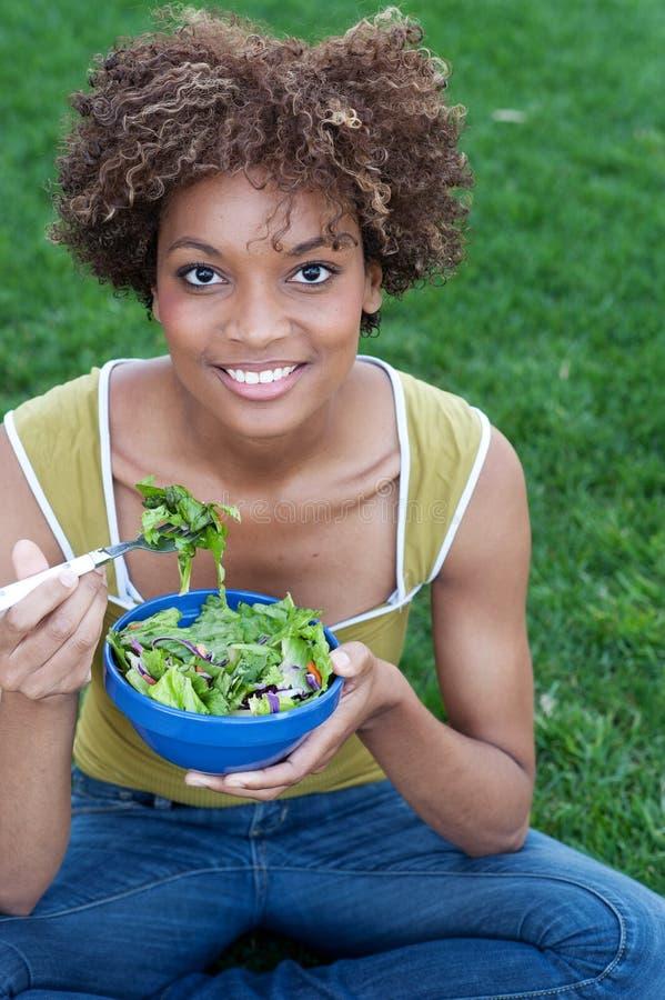 Mujer bonita del afroamericano que come una ensalada imagenes de archivo