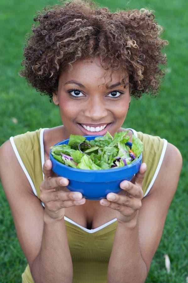 Mujer bonita del afroamericano que come una ensalada imagen de archivo