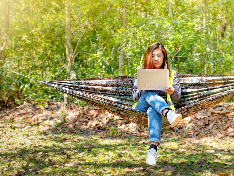 Mujer bonita del ingeniero utilizar su ordenador portátil en la hamaca a la conexión en línea con el compañero de trabajo también foto de archivo