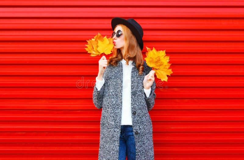Mujer bonita del otoño de la moda con las hojas de arce amarillas fotografía de archivo libre de regalías