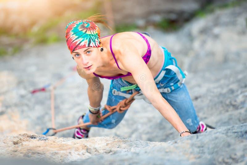 Mujer bonita deportiva que sube en la roca fotos de archivo libres de regalías