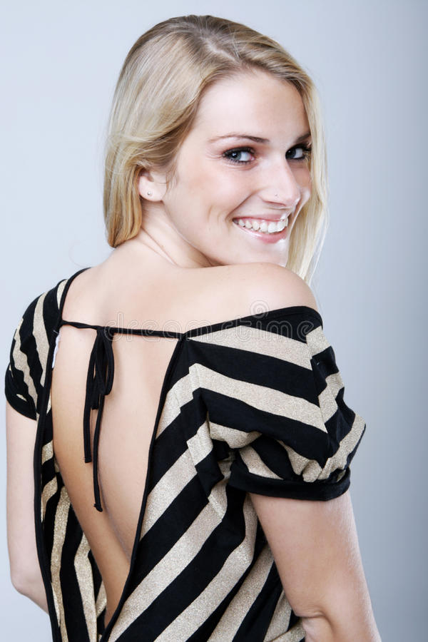 Mujer bonita en camisa muy escotada por detrás que sonríe en la cámara foto de archivo