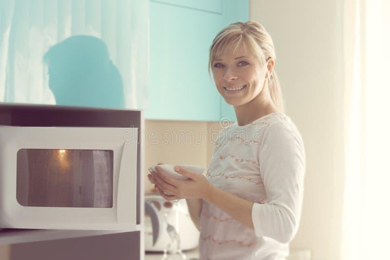 Mujer bonita en casa usando el horno de microondas foto de archivo