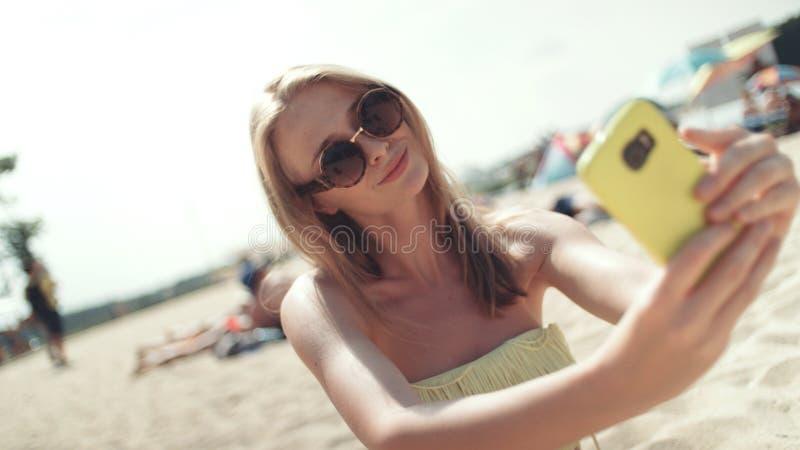 Mujer bonita en el bikini que se sienta en la playa y que toma un selfie fotografía de archivo libre de regalías