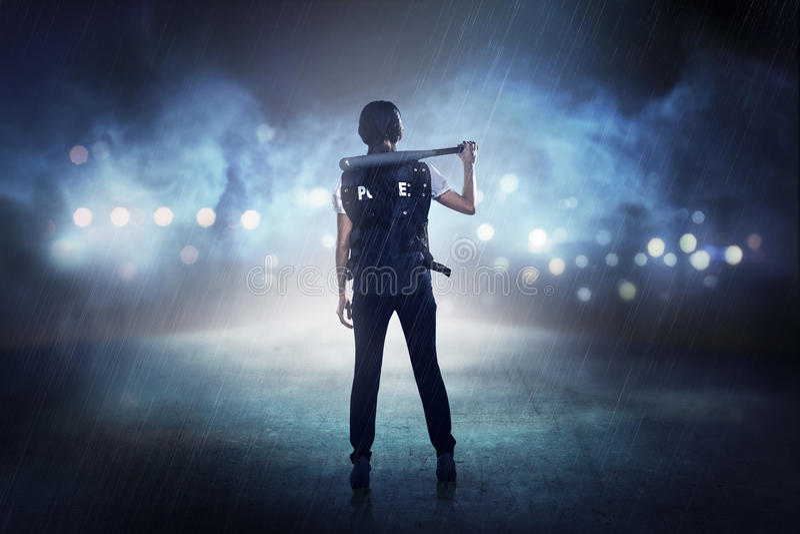 Mujer bonita en el chaleco de la policía que sostiene el bate de béisbol imagenes de archivo