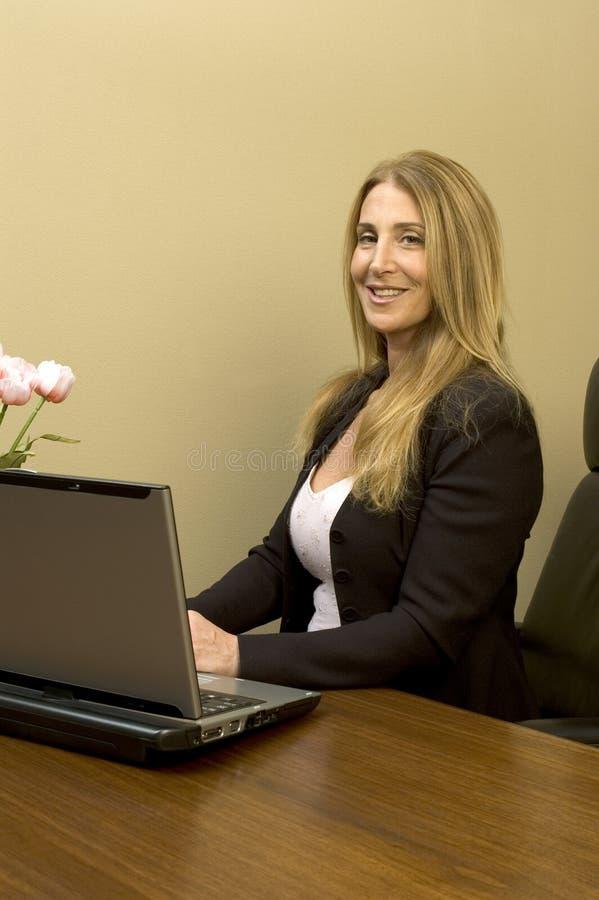 Mujer bonita en el escritorio fotos de archivo
