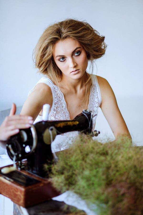 Mujer bonita En el estilo de Coco Chanel que se sienta en una máquina de coser foto de archivo