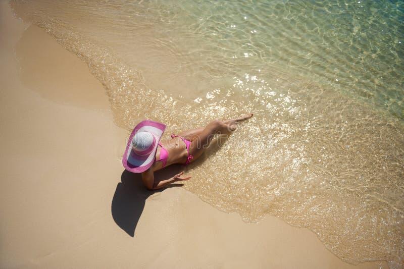 Mujer bonita en el sombrero que miente en la playa imagenes de archivo