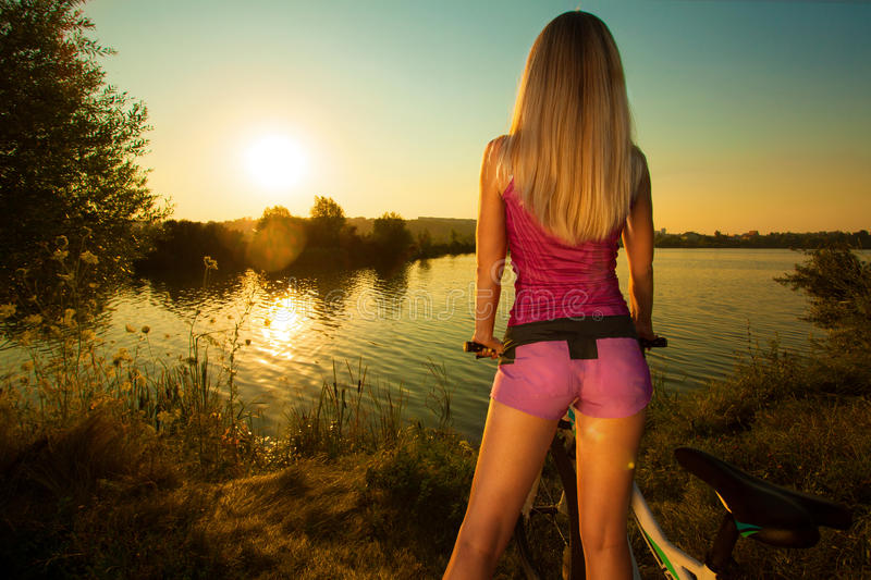 Mujer bonita en la bicicleta que se relaja en la puesta del sol imagen de archivo libre de regalías