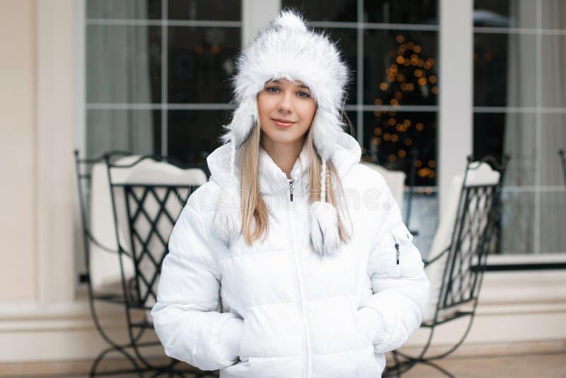 Mujer bonita en la chaqueta del invierno que se coloca cerca del café fotos de archivo libres de regalías